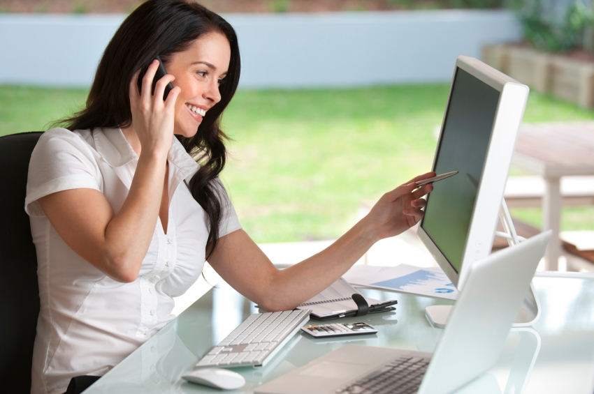Businesswoman talking on the phone smiling pointing at the computer screen